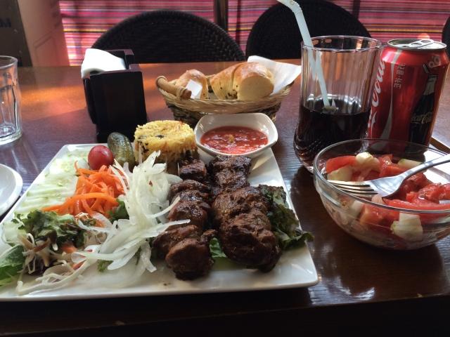 lamb kebabs, rice, bread, and plenty of veggies