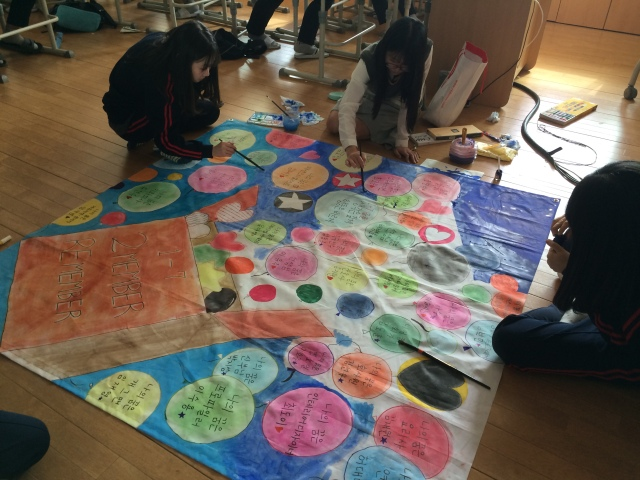students working on a banner for their class for the festival